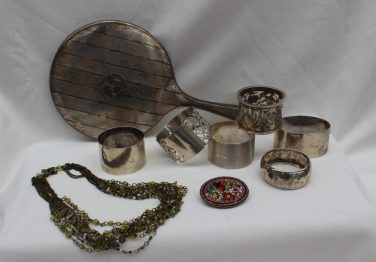 Assorted silver napkin rings, together with a silver backed hand mirror, micro-mosaic brooch and a necklace. Sold for £55 at Anthemion Auctions