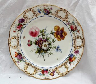 A Nantgarw plate, circa 1818-20, decorated in London, probably in the Bradley workshop. with an elaborate central floral spray with an anemone and rose flanked by insects in flight, a bright blue enamel line around the cavetto, the 'C' scroll border moulded with floral garlands picked out in gold, painted with floral sprays, impressed Nant-Garw C.W., 24.5cm diameter