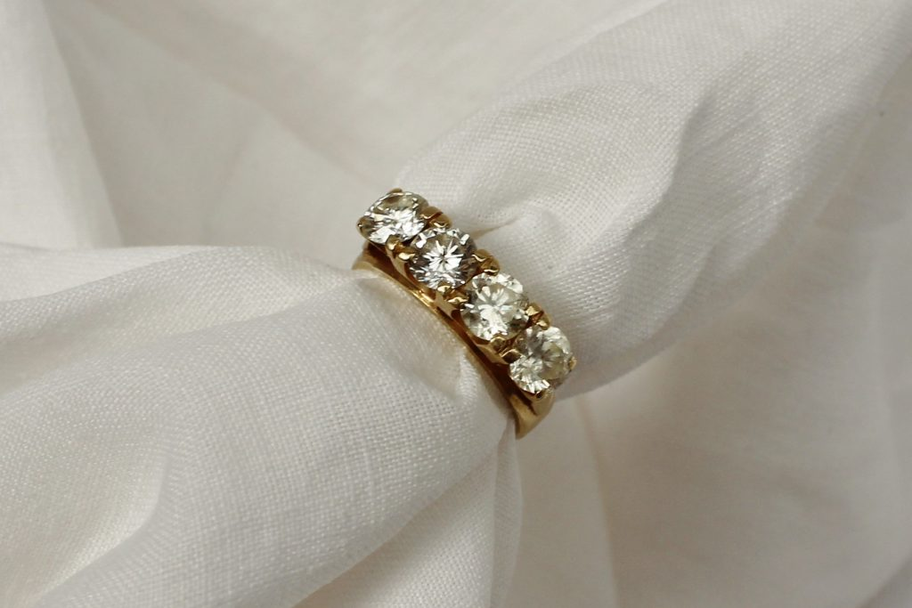 A four stone diamond ring set with round old cut diamonds each approximately 0.4 of a carat to a yellow metal claw setting and shank marked 18ct, approx 1.6 of a carat. Sold for £850 at Anthemion Auctions