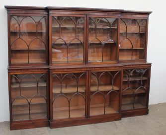 A 19th century mahogany breakfront library bookcase, the moulded cornice above four glazed doors with arched glazing bars, the base with four glazed cupboards with similar glazing on a plinth base 234cm wide x 178cm high x 42cm deep