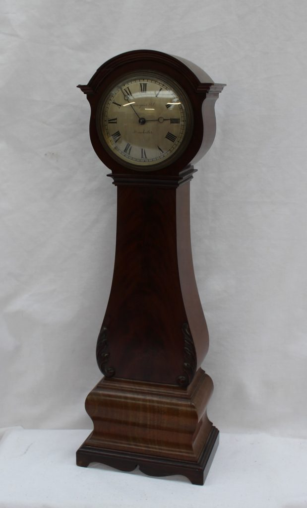 "A 19th century mahogany miniature longcase clock, the circular silvered dial with Roman numerals inscribed ""Finigans Ltd, Manchester"", above a baluster body and a shaped base with bracket feet, 43.5cm high. Lot 439 in our February 21st Fine sale"