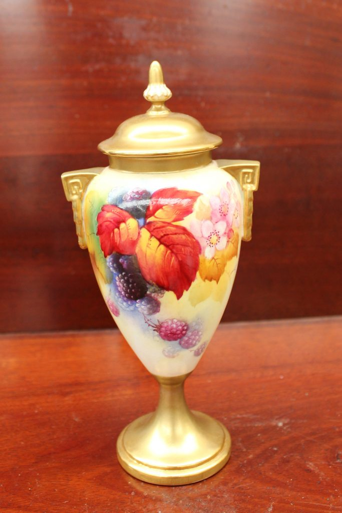 "A Royal Worcester twin handled vase and cover, painted with blackberries and leaves to an ivory ground, signed ""K Blake"", puce mark and date code for 1934. Sold for £140 at Anthemion Auctions"