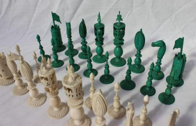 A 19th century Anglo Indian ivory chess set, one side natural, the other stained green, carved with flowers, leaves and beading, King 12cm high, pawn 6.5cm high
