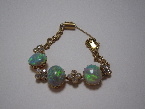 An opal and diamond bracelet set with three cabouchon cut opals, and four cross shaped clusters of four old cut diamonds and centre rose cut diamonds to a double row of belchers chains estimated weight of opals 10.75 carats diamonds 1.50 carat. Sold for £1,400 at Anthemion Auctions