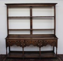 An 18th century South Wales oak dresser, the open rack with a moulded cornice above two shelves, the base with a planked top above an arrangement of seven drawers above ring turned legs and a pot board, 200cm wide x 216cm high. Sold for £1,250 at Anthemion Auctions