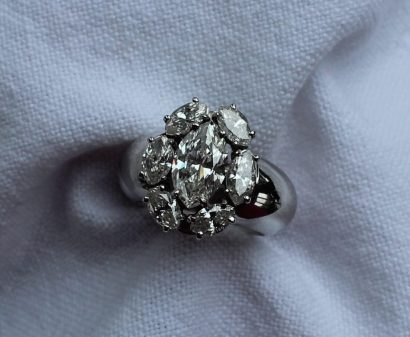 A diamond ring set with seven marquise shaped diamonds, the central stone with Antwerp World Diamond Centre certificate, (according to the certificate), the central stone weighs 1.55ct, vs1, white, measuring 10.47 x 6.29 x 3.80mm, surrounded by six marquise shaped diamonds measuring approximately 7mm x 4mm, to a white metal claw setting and shank, indistinctly marked, size K, approximately 12.5 grams. Estimates of £4,000 - 6,000