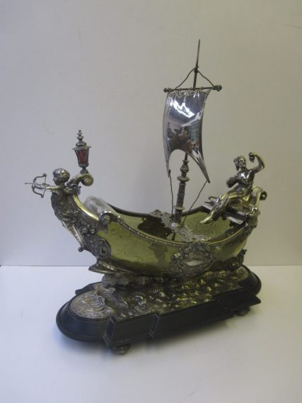 An impressive electroplated and etched green glass table centrepiece in the form of a sailing ship with a cupid figure head, a classical maiden seated eating grapes on the stern, on a choppy sea with a dolphin on flattened bun feet. 48 cms long x 52 cms high. Sold for £1,550 at Anthemion Auctions