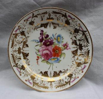 A Swansea porcelain plate, painted to the centre with a spray of garden flowers, the border with gilt scrolls and birds, label verso 'Swansea China, Sidney Heath Collection', 20.5cms diameter . Sold for £950 at Anthemion Auctions
