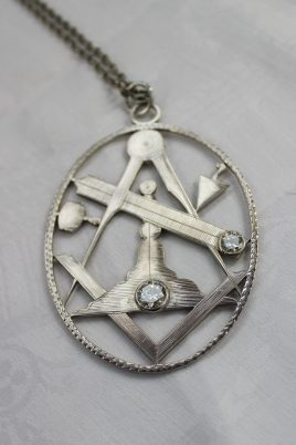 A white metal pendant of oval form pierced with Masonic symbols including a dividers, square, rule, mallet, set with a 1.5 carat solitaire diamond and another 1 carat solitaire diamond on a white metal chain. Sold for £4,800 at Anthemion Auctions