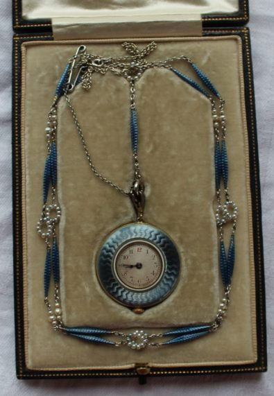 An Edwardian French 18ct gold, blue guilloche enamel and seed pearl fob watch with a silvered dial and Arabic numerals, the crown marked Fabrique Movado, the reverse of the case set with diamonds, on a matching seed pearl and enamel decorated white metal chain, in its original box for Mappin Brothers. Sold for £920 at Anthemion Auctions