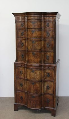 A reproduction walnut chest on chest with a moulded serpentine top above four long graduated drawers, the base with a brushing slide and three long graduated drawers on bracket feet, 83.5cm wide x 187 cm high x 52cm deep. Sold for £820 at Anthemion Auctions
