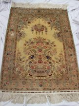 A Turkish silk rug, with a cream ground decorated with a vase of flowers and a hanging basket of flowers, the border with a green ground and floral border, 102cm wide x 147cm long. Sold for £1,300 at Anthemion Auctions