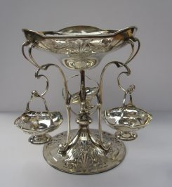 A George V silver table centrepiece, the shaped pierced top decorated with anthemions and leaves supported on scrolling uprights, the domed base with similar pierced decoration, with three hanging baskets, Sheffield, 1911, Walker and Hall, approx 1700 grams. Sold for £1,150 at Anthemion Auctions