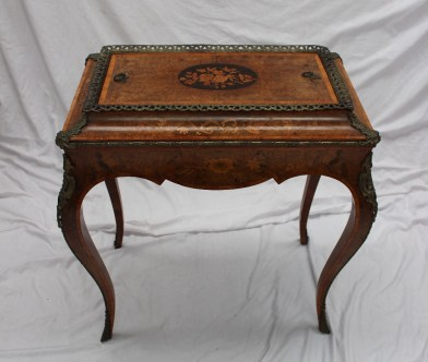 A French kingwood floral marquetry and gilt metal mounted jardiniere table, having a metal liner with a twin handled cross banded and oval inlaid cover, the sides profusely decorated on gilt metal mounted cabriole legs and sabot feet, 69 cm wide by 42 cm deep by 77 cm high. Sold for £750 at Anthemion Auctions