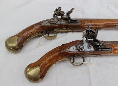 """A pair of long sea service flintlock pistols with tapering barrel, border-engraved lock with """"Tower"""" and """"GR"""" crowned, rounded pan, full stock, brass mounts, steel belt hook on one, and brass-tipped ramrod, 49 cm overall. Sold for £2,400 at Anthemion Auctions"""