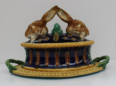 A remarkable Minton Majolica game tureen and cover, dated 1877, the base modelled as a decorative oval patè mould in yellow, ochre and blue, resting on a fixed basketwork tray or stand with rope handles, the cover with the heads of two hares and two mallard ducks realistically coloured and symmetrically arranged on a cobalt glazed dome studded with yellow florets, 31.5cm high, 46.5cm wide, impressed MINTONS with date cipher, model number 1990 impressed ***** The most splendid of all Majolica game tureens, this model has been attributed to Paul Comolera. An example was illustrated on the cover of the catalogue of the pioneering exhibition of Majolica held at Jeremy cooper Ltd in 1982. See also Karmason and Stacke, Majolica (1989), p.48. Sold for £13,000 at Anthemion Auctions
