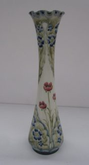 A William Moorcroft and MacIntyre slender vase decorated with red poppies and panels of blue forget-me-nots, printed mark and signature to the base. 24.5 cms high. Sold for £2,200 at Anthemion Auctions