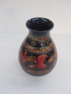 "A Moorcroft ""Pomegranate"" pattern baluster vase with banded floral decoration to a blue ground. Impressed and painted marks. 18 cms high. Sold for £1,850 at Anthemion Auctions"
