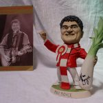 "A Richard Hughes resin grogg of Max Boyce, the figure wearing a rosette with the Prince of Wales feathers and holding a leek, signed by Max Boyce and Richard Hughes dated '99, 23cm high together with a Variety club of Great Britain programme, ""A tribute to Max Boyce at the Hilton on 21st August 1999. Sold for £150 at Anthemion Auctions"
