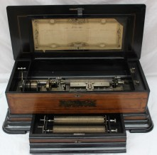 A Swiss rosewood inlaid interchangeable music box, the 28cm cylinder playing one of eight melodies on a comb, side wound mechanism with levers for repeat/change and stop/play, rectangular rosewood veneered case with ebonised mouldings and inlaid banding, the lid with marquetry inlaid ornament and brass carrying handles to the sides, a drawer below containing the two other cylinders, each numbered 26587, height 29 cm, length 80 cm. Sold for £2,600 at Anthemion Auctions