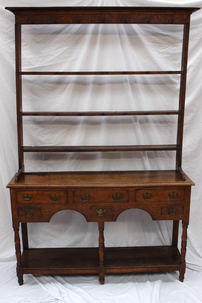 An 18th century South Wales oak dresser, the open rack with a moulded cornice above three shelves, the base with a rectangular planked top, an arrangement of six drawers and a pot board on ring turned columns and turned feet, 139cm wide by 213 cm high by 37 cm deep. Sold for £950 at Anthemion Auctions