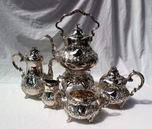 A Victorian silver four piece teaset, comprising hot water pot, teapot, sugar basin and cream jug, with chrysanthemum finials, the bodies profusely decorated with flowerheads and leaves, London, 1861, Edward & John Barnard approximately 2470 grams together with a similar electroplated spirit kettle on stand. Sold for £1,650 at Anthemion Auctions