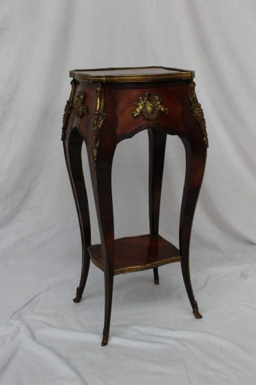 A French Kingwood and gilt metal mounted torchere, the shaped rectangular top above a single drawer on hipped cabriole legs and gilt metal mounted sabot feet united by a shelf, 29.6cm wide x 23.5cm deep x 72.5cm high. Sold for £1,600 at Anthemion Auctions