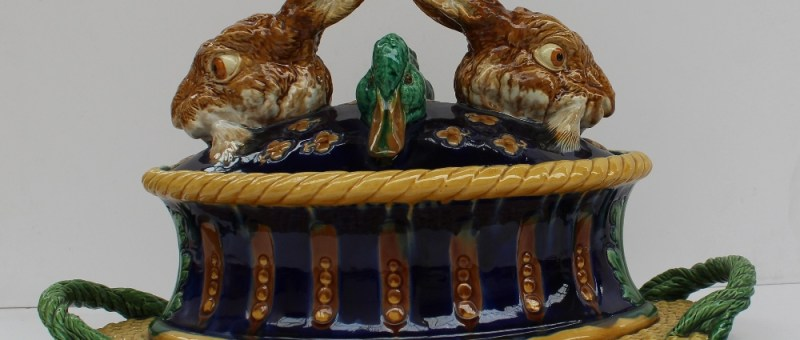 A remarkable Minton Majolica game tureen and cover, dated 1877, the base modelled as a decorative oval patè mould in yellow, ochre and blue, resting on a fixed basketwork tray or stand with rope handles, the cover with the heads of two hares and two mallard ducks realistically coloured and symmetrically arranged on a cobalt glazed dome studded with yellow florets, 31.5cm high, 46.5cm wide, impressed MINTONS with date cipher, model number 1990 impressed. Sold for £13,000 at Anthemion Auctions