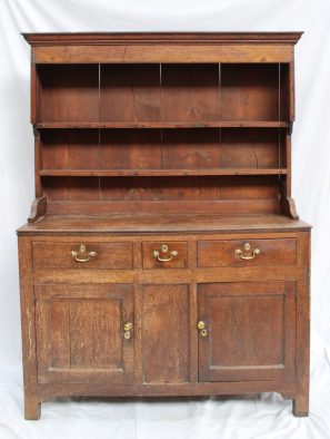 An 18th century oak North Wales dresser, the rack with a moulded cornice and planked back with two shelves, the base with a planked top above three drawers and two cupboards on stiles, 136 cm wide. Sold for £1,000 at Anthemion Auctions