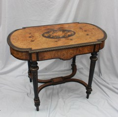 A Victorian walnut centre table, the gilt metal mounted shaped top with a central oval marquetry panel of flower heads and leaves, above a single drawer on tapering ebonised legs and peg feet. Sold for £820 at Anthemion Auctions