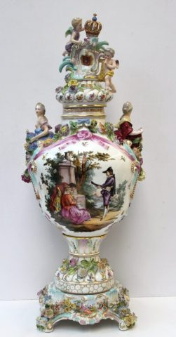 A Saxonion porcelain (Carl Thieme) flower encrusted vase and cover, blue crossed lines and T Mark, late 19th/20th century, the spiral gadrooned cover with a putto and Saxony, the vase shoulder applied with classical maidens above moulded pink ribbons, painted front and back with genre scenes in the manner of Watteau, on a conforming socle, 69cm high. Sold for £720 at Anthemion Auctions