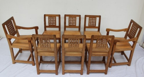 "Robert Thompson of Kilburn, ""Mouseman"" - A set of eight light oak dining chairs with lattice back and studded seat on carved legs and square section feet, each carved with the trademark mouse, includes two carvers (8). Sold for £2,400 at Anthemion Auctions"