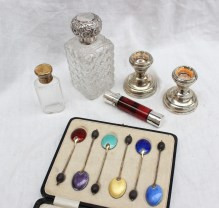 A silver topped scent bottle together with a silver gilt topped scent bottle, a cranberry glass and white metal double ended scent bottle, pair of silver desk candlesticks and a cased set of silver gilt enamel spoons