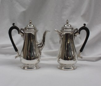 A George VI silver coffee pot, with a turned finial and domed top above a baluster body and spreading foot, together with a matching hot water pot, Sheffield, 1944, Harrison Brothers & Howson (George Howson), approximately 870 grams