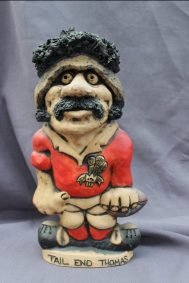 """A John Hughes pottery Grogg of """"Tail end Thomas"""", in a red Welsh jersey with the No.8 on the reverse, Signed to the base, 32cm high. Sold for £130 at Anthemion Auctions"""