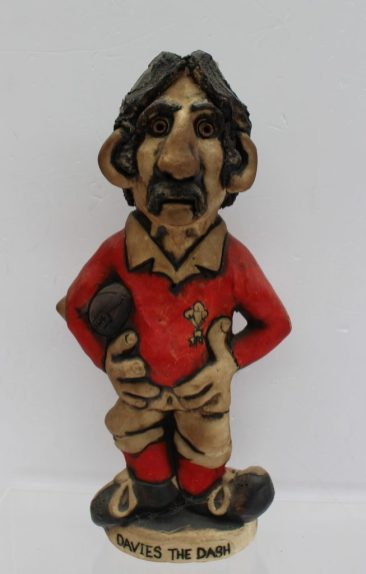 "A John Hughes pottery Grogg titled ""David the Dash"" in a red Welsh jersey with No.11 on the reverse, signed and dated 1976, 33cm high. Sold for £100 at Anthemion Auctions"