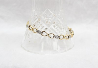 An 18ct yellow and white gold diamond set tennis bracelet, with figure of eight links set with nine round brilliant cut diamond each approximately 0.05 of a carat, 20.5cm long, approximately 22.7 grams. Sold for £1,300 at Anthemion Auctions
