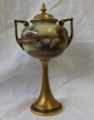 A Royal Worcester porcelain two-handled pedestal vase and cover of urn form, shape No. 2736, painted with sheep by a lake, a cottage in the distance, and gilt, by Harry Davis, date code for 1924, 23 cms high. Sold for £460 at Anthemion Auctions