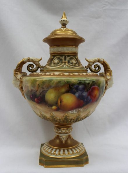 A Royal Worcester twin handled vase and cover, hand painted with apples, pears, cherries and grapes signed by Ricketts with two mask and scrolling leaf capped handles, with gilt heightened moulded decoration to the neck and cover, raised on a spreading circular foot on a square base with re-entrant corners, printed puce marks to base, model no.1572, and date code for 1914, 28cm high. Sold for £820 at Anthemion Auctions