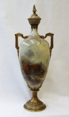 A Royal Worcester porcelain twin handled vase and cover, the domed cover with a flame finial above angular twin handles and a shouldered vase painted with highland cattle in a naturalistic setting, signed J Stinton on a spreading foot, puce mark, No.247 date code for 1920, 34.5cm high. Sold for £1,250 at Anthemion Auctions