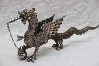 22nd August - Silver Lot 212. A Welsh Dragon table lighter the silver plated body of the dragon finely formed with wick in mouth, a lighter in chest formed as an arrow, the large wings (one inscribed `YE DRAGON OF WANTLEY`) sweeping back over long twisted horn tail, raised on four silver plated feet overall length 54cm long x 16.5cm high