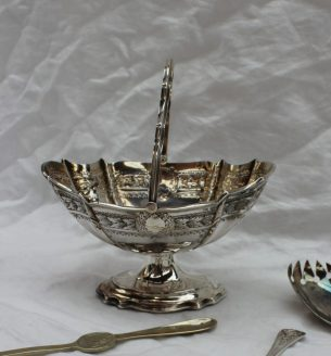 22nd August - Silver Lot 215. An Edward VII silver swing handled pedestal bowl, the oval tapering body decorated with cast leaves on a spreading foot, Sheffield, 1901, Walker & Hall together with silver sauce ladles, silver sugar nips, silver sifting spoon, silver coffee spoons, silver and glass salad servers etc weighable silver approximately 480 grams