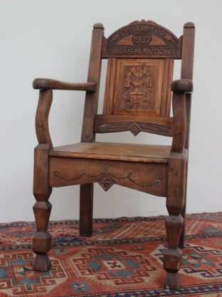 "An early 20th century Eisteddfod chair, the arched back carved for ""Dinas Mawddwy Eisteddfd 1937"" the central panel carved with a vase of flowers, with a planked seat on square tapering legs, 108.5cm high. Sold for £360 at Anthemion Auctions"