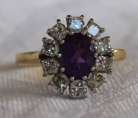 22nd August Fine Sale - Jewellery Lot 1. An amethyst and diamond ring, the oval faceted amethyst surrounded by ten princess cut diamonds to a white metal claw setting and 18ct yellow gold shank