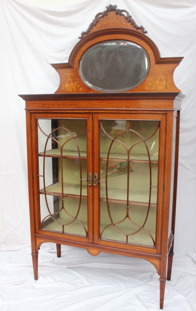 An Edwardian mahogany mirror backed display cabinet, the raised back with a scrolling carved cornice with marquetry panel of a basket of fruit and flowers with an oval mirror plate, the base with a rectangular top, bevelled glass sides and a pair of glazed doors with glazing bars on square tapering legs, 205cm high x 46cm deep x 107cm wide. Sold for £170 at Anthemion Auctions