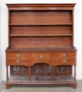 A 19th century South Wales oak dresser, with a moulded cornice, with two shelves, the base with a planked top and three drawers, ring turned columns, bracket feet and a pot board, 171.5cm wide x 198.5cm high x 41cm deep. Sold for £360 at Anthemion Auctions