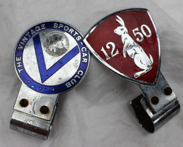 An Alvis 12/50 enamel car badge by Desmo, of shield shape with a Hare to a red enamel ground together with a Vintage Sports Car Club badge with St Christopher roundel and blue enamel decoration. Sold for £50 at Anthemion Auctions