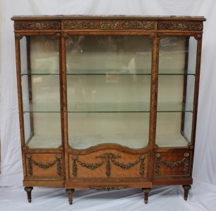 22nd August Fine Sale - Furniture Lot 376. A 19th century French marble topped kingwood, parquetry and ormolu mounted breakfront display cabinet, with a breakfront marble top above an ormolu apron cast with cupids and cornucopia, a single glazed door with glazed front and side panels the base decorated with gilt metal swags on tapering feet, 143cm wide x 40cm deep x 155cm high