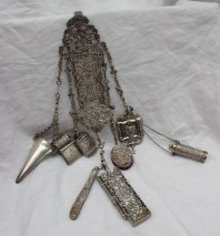 22nd August - Silver Lot 236. A 19th century continental white metal chatelaine, with Victorian silver and white metal fittings including a vinaigrette, vesta case, pin cushion, note case, pen knife, posy holder, tape measure, needle case etc, overall approximately 246 grams