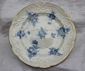 22nd August - Welsh Ceramics Lot 260. A Nantgarw porcelain plate painted with sprays of cornflower blue flowers to a moulded border and scalloped gilt rim, impressed Nantgarw C.W., 25cms diameter, bears a label for Spence-Colby Collection Donnington Hall